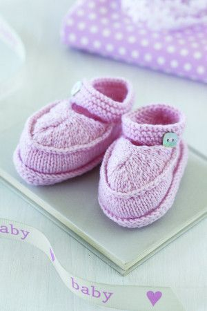 Knitted baby boots with a strap and button fastening
