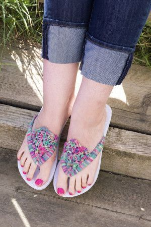 A pair of flip flops decorated with a bright boho crochet trim