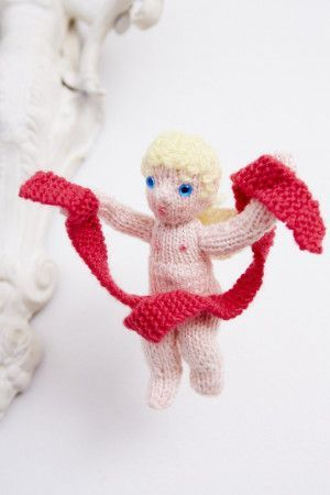 Knitted cupid toy holding a knitted ribbon banner