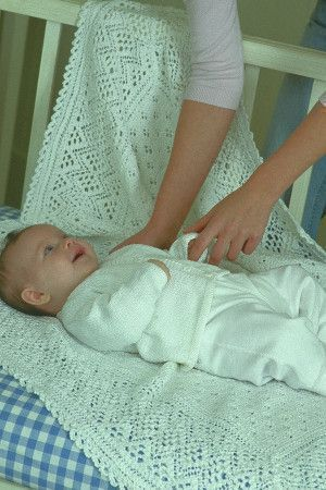 Baby resting on a knitted lace blanket