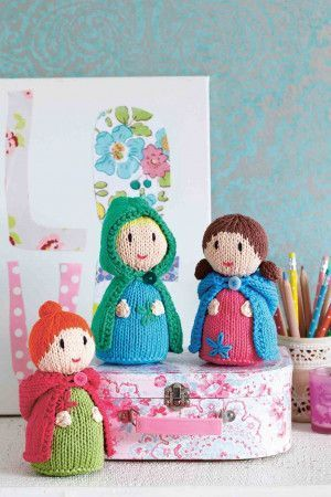A trio of knitted doll toys wearing capes