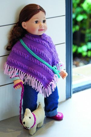 Doll dressed in a purple poncho with a small knitted dog toy
