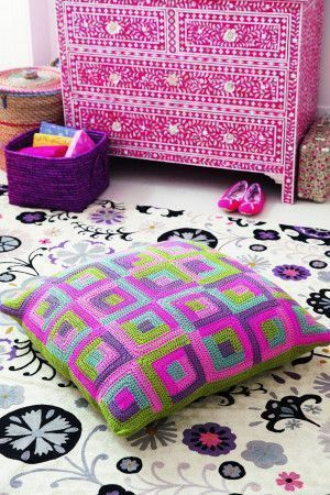 Large crocheted floor cushion with a retro design