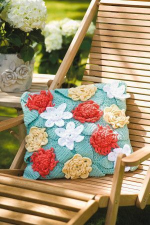 Crochet cushion with crocheted flowers and leaves pattern