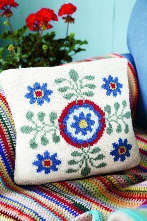 Jane Crowfoot square knitted cushion decorated with a flower motif