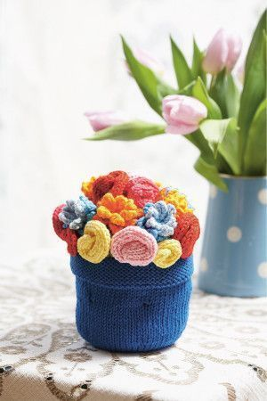 Plain knitted flower pot with array of bright flowers