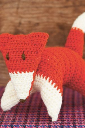 Crocheted fox toy with triangular face and two-tone body