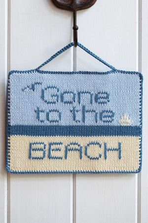 Knitted seaside hanging sign in blues and cream with lettering, boat and seagull
