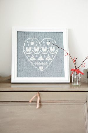 Framed knitted sampler within a heart in white and silver yarn