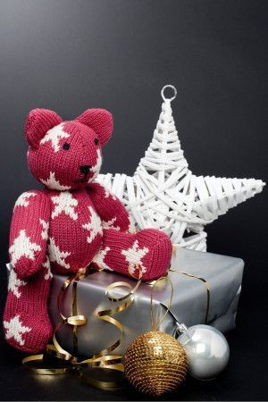 Red knitted teddy bear with white star design over head, body and legs