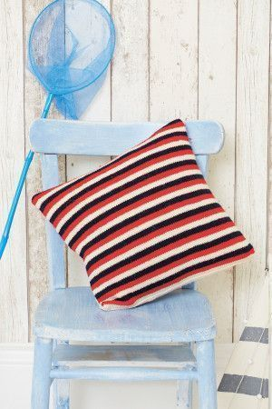 Knitted cushion cover with thin stripes in three colours on one side and cable on reverse