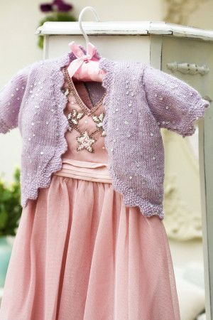 Sparkly knitted bolero cardigan for a child with scalloped edging
