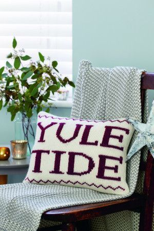 Rectangular cushion with Yuletide knitted across the front