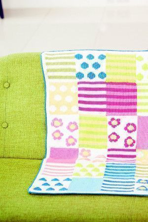Knitted colourful baby blanket with spots, stripes and flowers