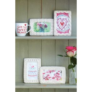 Four crocheted photo frame designs in cream yarn
