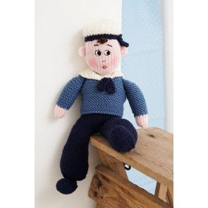 Knitted sailor in traditional uniform with cute cap and embroidered face