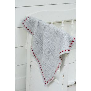 Baby blanket with cables and cross stitch design in contrast colour