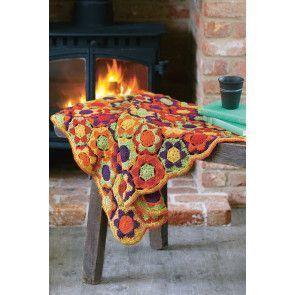Crocheted hexagon blanket in bright orange, green, yellow and purple