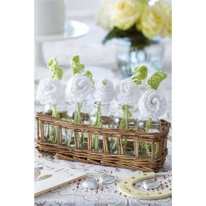 Basket of white crocheted flowers with green leaves for wedding breakfast table