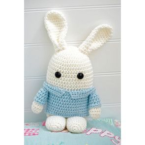 Crocheted white toy bunny wearing pale blue jacket with collar