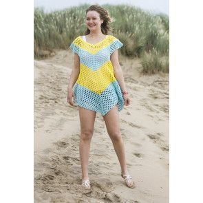 Lady on a beach wearing a bright poncho with chevron pattern