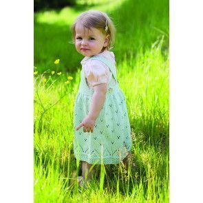 Knitted baby girl's dress with eyelets and cross-over straps